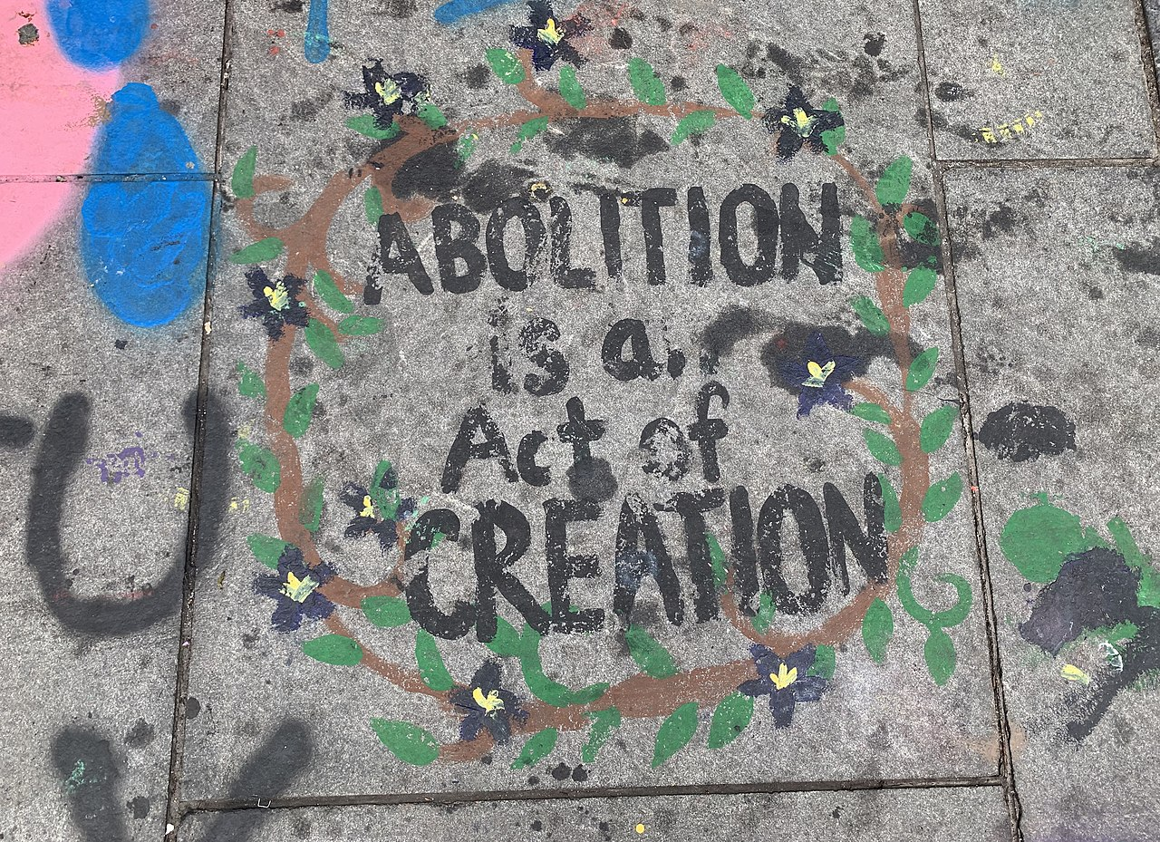 "Text in a sidewalk chalk mural reads: ""Abolition is a act of creation,"" and is surrounded in green vines and yellow flowers."